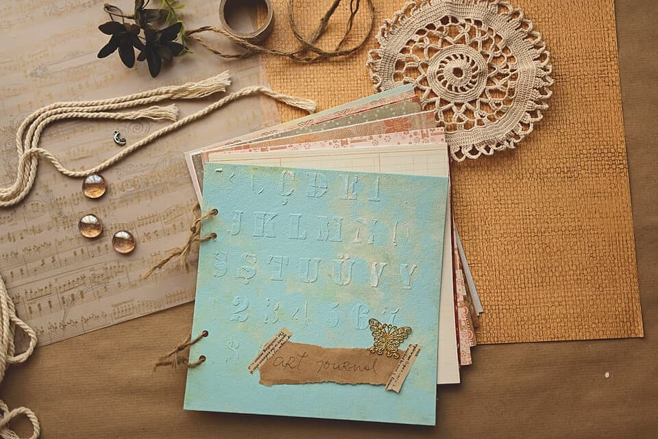 A photo of a DIY art journal on a brown aper. the journal is light blue and bound with a twine