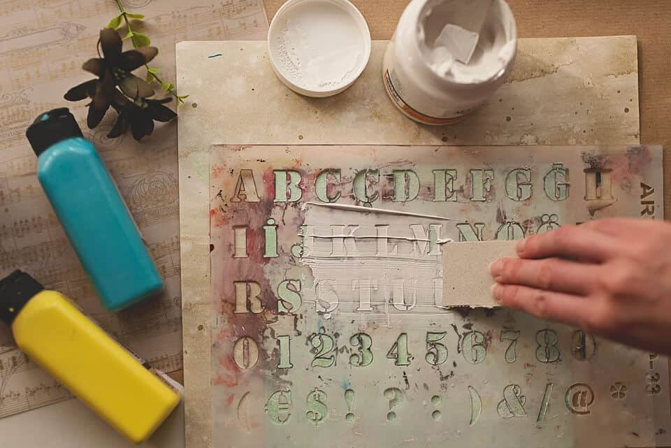 A PHOTO OF USING A STENCIL AND GESSO ON THE COVER OD THE DIY ART JOURNAL