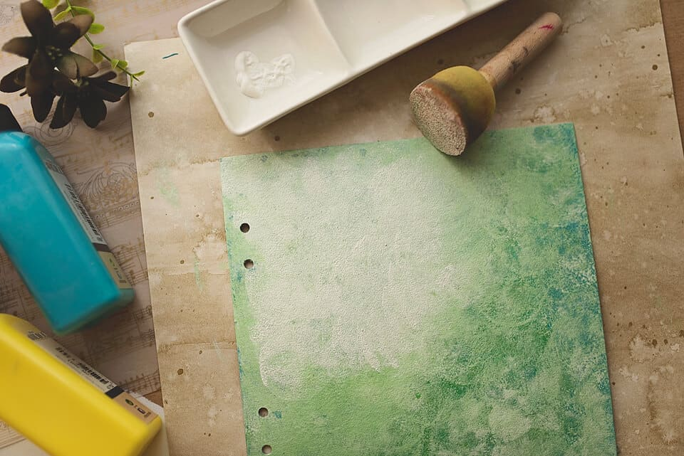 A COVER FOR A DIY ART JOURNAL PAINTED IN GREEN PAINT AND GESSO