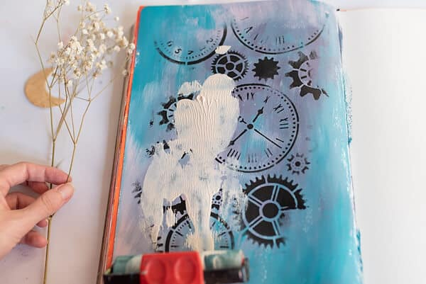 applying white paint with a brayer in an art journal