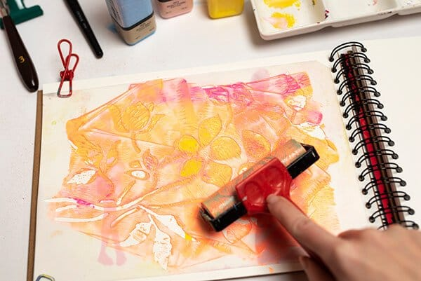 applying acrylic paint with a stencil using a brayer