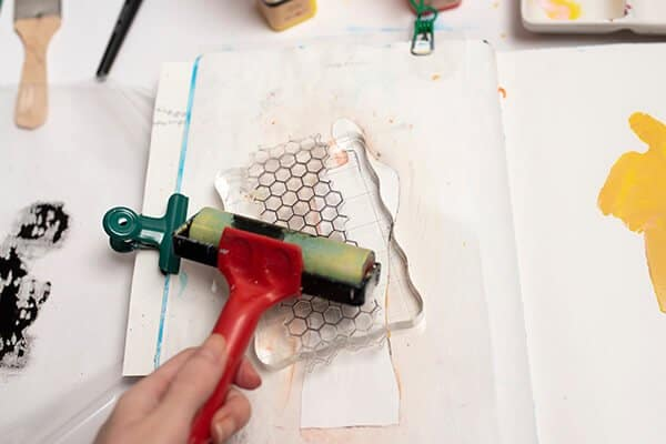 applying acrylic paint on a stamp with a brayer