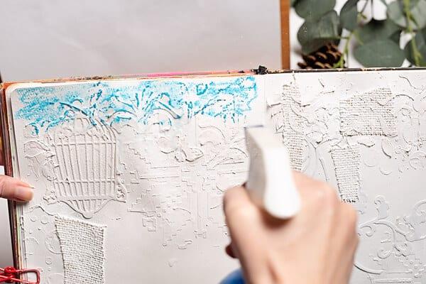 spraying water on art journal page