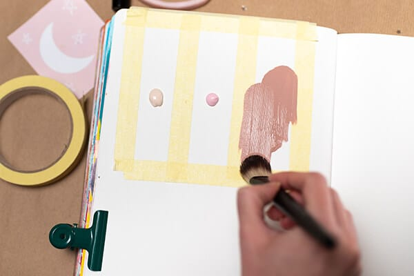 painting with paintbrush over masking tape