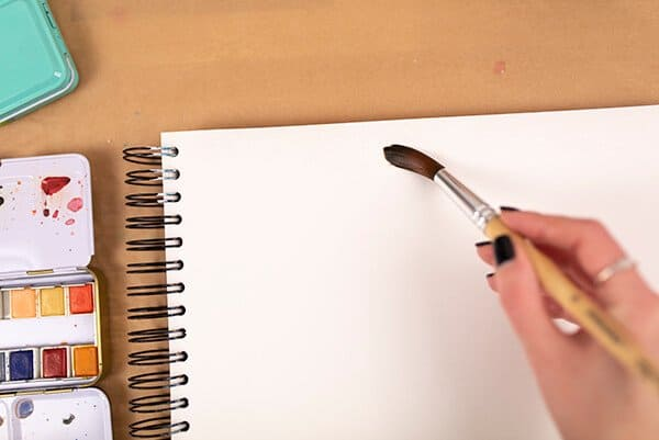 putting water on a page with a brush