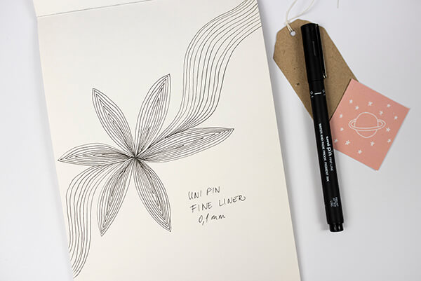 paper with flower doodles and a black pen